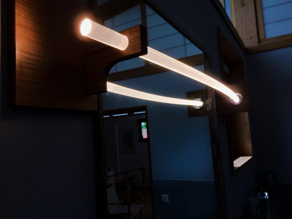 Eine Nûon 20 Wand- und Deckenleuchte in einer Holzfassung als Badspiegelleuchte positioniert. Leuchtkörper aus massivem Plexiglas.