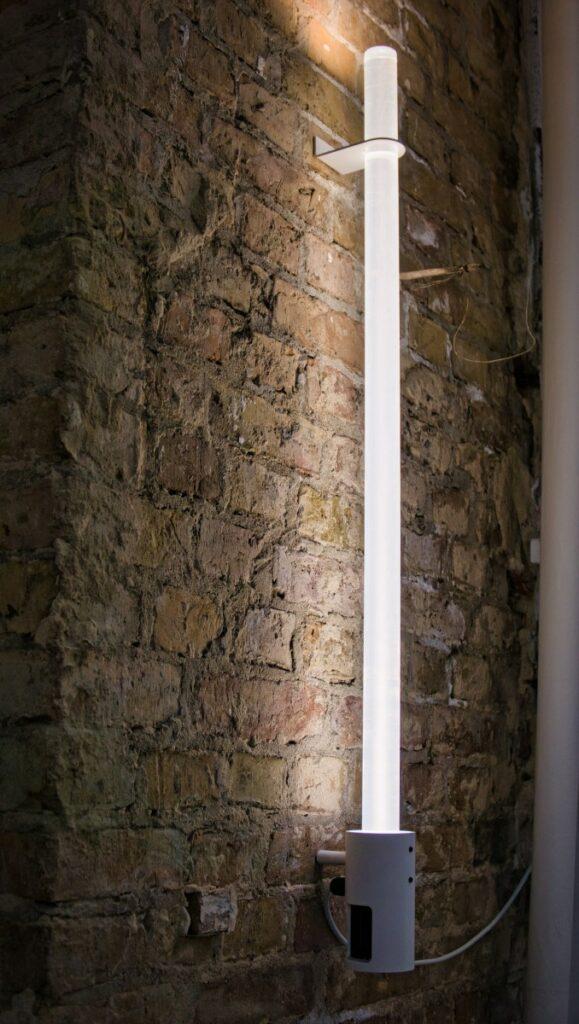 Nûon 40 Wandleuchte aus Plexiglas an einer Backsteinwand. Wandinstallation senkrecht