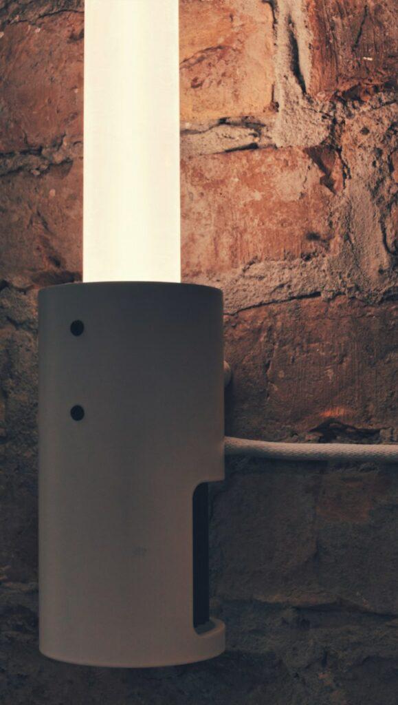 Nûon 40 Wandleuchte aus Plexiglas an einer Backsteinwand. Nahaufnahme auf Sockel mit Kühlkörper Wandinstallation senkrecht